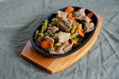 Stewed meat with beans and carrots. Stewed meat served in a frying-pan cooked with vegetables Stock Image