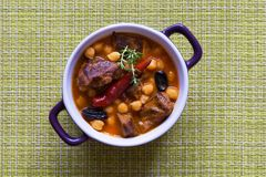 Stewed meat with bulgur and chickpeas in red sauce stock image