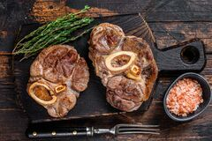 Free Stewed Meat On The Bone Osso Buco Beef Shank, Italian Ossobuco Steak. Dark Wooden Background. Top View Stock Images - 207051024