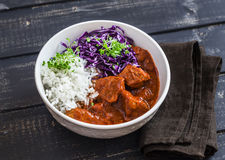 Stewed meat with rice and red cabbage in a white bowl on a dark wooden background. Stock Photo