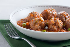 Stewed meatballs with peas, tomato and onion Stock Photo