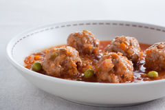 Stewed meatballs with peas, tomato and onion. Royalty Free Stock Photos