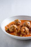 Stewed meatballs with peas, tomato and onion. Royalty Free Stock Image