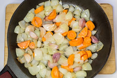 Stewed onions, carrots and garlic in a frying pan. 