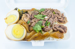 Stewed pork leg on rice. Stewed pork leg on rice in foam box Stock Image