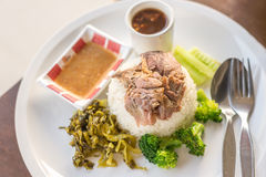 Stewed pork leg on rice on wooden table, asian food. Stock Photography