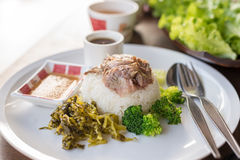 Stewed pork leg on rice on wooden table, asian food. Stock Image