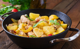 Stewed potatoes with meat and vegetables in a roasting tin. Stock Photo