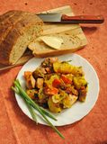 Stewed potatoes with sausages and vegetables. Rural lunch with homemade bread Stock Images