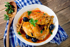 Stewed rabbit legs with black olives and fresh herbs. Stock Image
