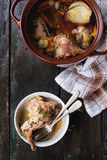 Stewed rabbit with vegetables. Brown ceramic pot with stewed rabbit with bouillon, vegetables and herbs, and bowl with rabbit leg, served with kitchen towel and Stock Images
