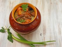 Stewed rabbit with vegetables Goulash in Copper Pot on shabby Wooden background, roasted beef meat with carrot, leek, onion in rou. Stewed rabbit with vegetables Royalty Free Stock Images