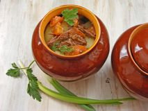 Stewed rabbit with vegetables Goulash in Copper Pot on Wooden Surface, roasted beef meat with carrot, leek, onion in round ceramic. Stewed rabbit with vegetables Royalty Free Stock Photo