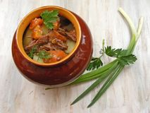 Stewed rabbit with vegetables, Venison Goulash in Copper Pot on Wooden Surface, roasted beef meat with vegetables and herbs in rou. Stewed rabbit with vegetables Stock Image