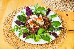Stewed red rice, turkey on circle from salad leaf. royalty free stock images