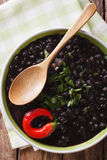 Stewed spicy black beans close up in a bowl. Vertical top view Royalty Free Stock Photography