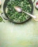 Stewed szpinak z kremowym kumberlandem w kucharstwo garnku z łyżką na nieociosanym tle, odgórny widok fotografia royalty free