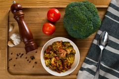 Stewed tomatoes with broccoli in a plate on a wooden background royalty free stock photo