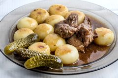 Stewed turkey meat served with silesian dumplings and sauce. Stewed turkey meat served with silesian dumplings, pickled cucumber and sauce Royalty Free Stock Photos