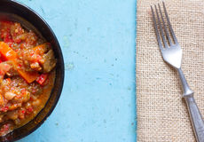 Stewed vegetables in a black plate and fork on mats on a blue background Stock Photography