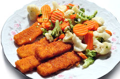 Stewed vegetables and fish fingers on a plate. Stewed carrots, broccoli, cauliflower and fried fish fingers on a plate Royalty Free Stock Images