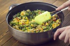Stewed warzywa w smaży niecce na drewnianym tle, ręk warzywa fotografia stock