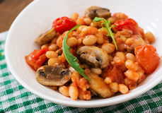 Stewed white beans with mushrooms and tomatoes with spicy sauce Stock Image