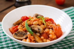 Stewed white beans with mushrooms and tomatoes with spicy sauce Stock Photos