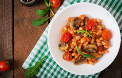 Stewed white beans with mushrooms and tomatoes with spicy sauce in a white bowl. Stock Images