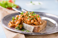 Stewed white beans in tomato sauce on toasted bread Stock Images