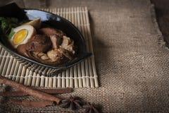Stewed wieprzowina w czarnym miejscu przed na, jajka i i worka i drewna tłem zdjęcia stock
