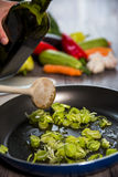 Stewing leek slices in a frying pantable Royalty Free Stock Photo