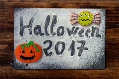 SThe words. Sweet terror is coming. The words `Halloween 2017` on a slate with flour and cookies Stock Photo