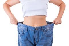 Stia il concetto a dieta Donne esili in grandi jeans che mostrano riuscito peso Immagine Stock