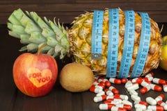 Stia l'alimento a dieta Ananas maturo e nastro di misurazione su un fondo di legno Pillole e integratori alimentari Per voi Fotografie Stock Libere da Diritti