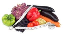 Stia l'alimento a dieta Verdure e nastro di misurazione su un fondo bianco Fotografie Stock Libere da Diritti