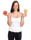 Stia la donna a dieta che tiene una mela e una ciambella Immagini Stock