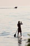 Stia su praticare il surfing della pagaia Fotografia Stock Libera da Diritti