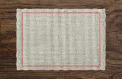 布料桌被撕毁的边缘织品,红色stich十字架 库存图片