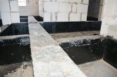 Stichtingsbitumen het waterdicht maken De bouw van het de bouwhuis met het waterdicht maken nevel-op teer stock afbeelding