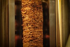 Preparing Shawarma cutting meat. A stick of Arab shwarma in front of the grill, a popular Middle Eastern snack Stock Photo
