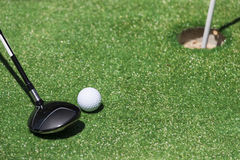 Stick with a ball on an artificial golf Royalty Free Stock Photo