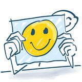 Stick figure behind a note paper and a happy face on it. Stick figure behind a note paper and a happy yellow face on it Royalty Free Stock Photos