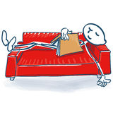 Stick figure with a book sleeping on a sofa bed Royalty Free Stock Photography