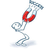 Stick figure with magnet and success Royalty Free Stock Photo
