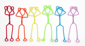 Stick figures relaxing - hands behind heads. Colorful pipe cleaner stick figures seen from above, relaxing with hands behind head as they lay down Royalty Free Stock Photos