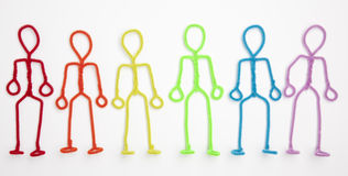 Stick figures relaxing - standing arms sides. Rainbow colored pipe cleaner stick figures standing with arms at their sides Royalty Free Stock Images