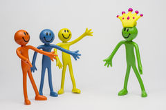 Stick men busines crowning. Plastic stick men representing work , corporate or people . Welcoming new leader into place of work. represents teamwork, success and Royalty Free Stock Photos