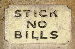 Stick no Bills sign. Historic sign painted onto wall alongside a London pavement with the instruction stick no bills meaning that posters should not be pasted Stock Images