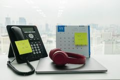 Stick note call back message and check e-mail on IP phone and November calendar for employee reminder with notebook computer an royalty free stock photography